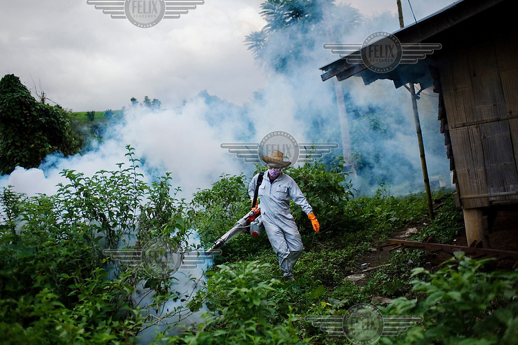 A man fogs a Karen village against mosquitoes in Northern Thailand. The technique of fogging, or area spraying, which aims at killing mosquitoes by contact with the insecticide in the air, has had very limited success in malaria control.