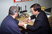Police surgeon attending to a suspect at a police station. The suspect is involved in a serious crime and the doctor is taking a sample of blood for analysis which may be used in evidence. This image may only be used to portray the subject in a positive manner..©shoutpictures.com..john@shoutpictures.com