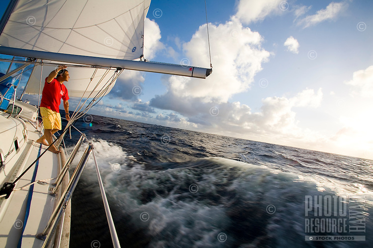 Man at the rail of a sailboat at speed in the trade winds, during a Pacific crossing