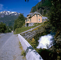 Couple walking along narrow road passing typical wooden clad house in the Norwegian fjords. Torrents of water are racing under nearby bridge from with the snow clad mountains in the background.circa 1976
