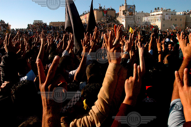 Amidst chaotic scenes, thousands of Palestinians converge on the Muqata compound ahead of the burial of Yasser Arafat. Here, the crowd gestures the V for victory sign.