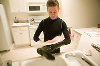 Jockey Julien Leparoux cleans his riding boots in his rented apartment's kitchen sink in Saratoga Springs, NY, United States, after returning from the day's early morning practice rides, 4 August 2006.