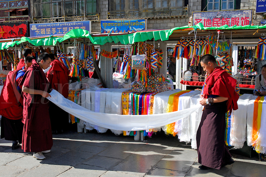 Tibetan Buddhist monks folding a white silk scarf, or khata, to be used as an offering in the monastery, at a market stall in Barkhor Square, Lhasa, Tibet.