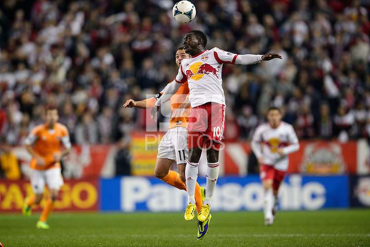 Brad Davis (11) of the Houston Dynamo goes up for a header with Lloyd Sam (10) of the New York Red Bulls. The Houston Dynamo defeated the New York Red Bulls 2-1 (4-3 on aggregate) in overtime of the second leg of the Major League Soccer (MLS) Eastern Conference Semifinals at Red Bull Arena in Harrison, NJ, on November 6, 2013.