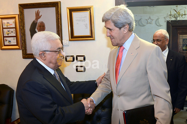 Palestinian President Mahmoud Abbas (L) shakes hands with US Secretary of State John Kerry (R) in Amman on May 27, 2013. Kerry unveiled a plan to boost the Palestinian economy by attracting $4 billion in private investment, saying it could transform the lives of the people. Photo by Thaer Ganaim