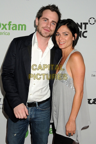 "RIDER STRONG & ALEXANDRA BARRETO .Oxfam America and Esquire House LA Host ""The Oxfam Party"" held at Esquire House LA, Los Angeles, California, USA, .18th November 2010..half length black white shirt beard facial hair jeans sleeveless silver grey gray top married couple husband wife .CAP/ADM/BP.©Byron Purvis/AdMedia/Capital Pictures."