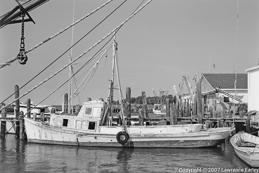 The LINDA, here tied up at the docks of the Smith and Son Fish House in Atlantic, was built by Ambrose Fulcher in 1939 for John Weston Smith and named for Smith's daughter.  She was built as a runboat but was also used for shrimping, clamming and crabbing.  Wooden workboats require constant upkeep, and sometimes the amount of work required exceeds the usefulness of the boat.  In 2010, the LINDA lay half sunk in the harbor.