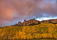 Uncompahgre National Forest, Colorado: Rainbow and storm clouds over peaks of the Cimarron Range and fall colored aspen groves at sunset