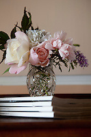 A posy of garden flowers is arranged in a cut glass vase