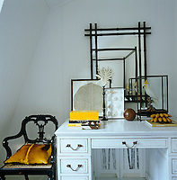 The white dressing table in the bedroom displays an eclectic array of objects