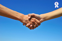 Woman and teenager handshake, on blue sky (Licence this image exclusively with Getty: http://www.gettyimages.com/detail/103933313 )