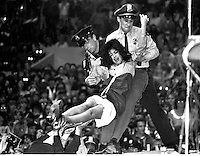 Unidentified female fan is carried off the stage by police security during the preformance  of the Beatles at the Cow Palace in San Francisco, Ca. (Aug 31, 1965 photo by Ron Riesterer)