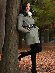 Fashionably dressed for autumn season, beautiful smiling young woman wearing a green coat, leaning against a maple tree in a park.