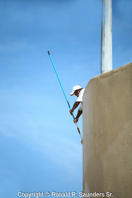 WORKER PAINTS TALL STRUCTURE
