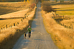 A young woman and her dog run along a country road in Teton Valley, Idaho.