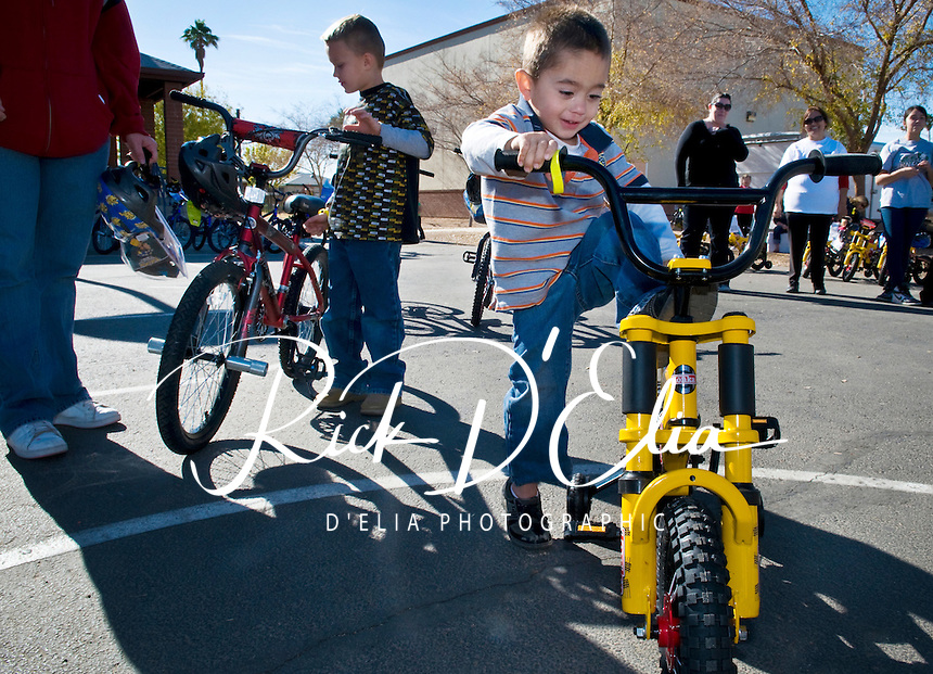 Andrew Roberts, 3, Phoenix, climbs aboard his new bike that he received from the Pedal Power Foundation at Whittier Elementary School in Phoenix, Ariz. The foundation gave away 220 new bikes and helmets to children in need around Phoenix, the most in a holiday season in the 11-year history of the organization.  Donors helped the foundation buy the bikes and helmets at a big discount from manufacturers.