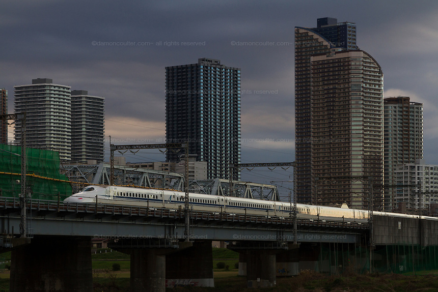 An N700 Series Shinkansen or Bullet Train crosses a bridge with the skyscrapers of Musahi Kosugi behind, Kanagawa , Japan, Friday December 14th 2018