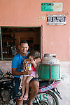 Luiz Closemilton Alves de Souza with 2-year-old daughter Yasmin Oliveira de Souza in their family's bar and tire station..Conjunto Palmeiras, Fortaleza, Ceara, Brazil.Photo: Eduardo Martino / Documentography