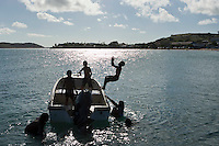 Kids leaping off a boat into the waters of Thursday Island, Torres Strait Islands, Queensland, Australia