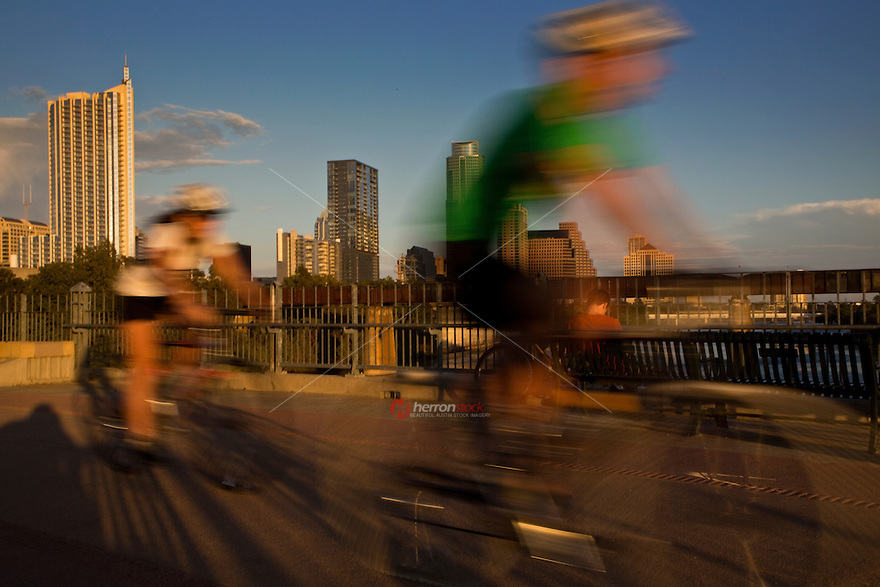 Bicyclists peddle across the Lamar Street Pedestrian Bridge overlooking the Austin Skyline