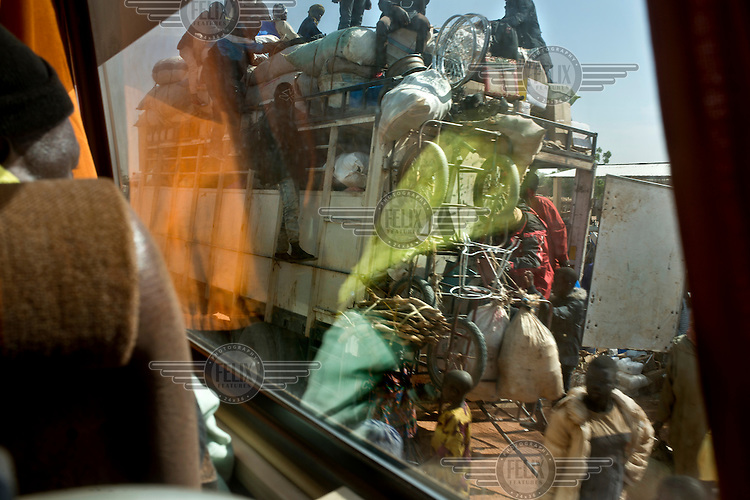 A view through the window of a bus of a lorry loaded with people and sacks.