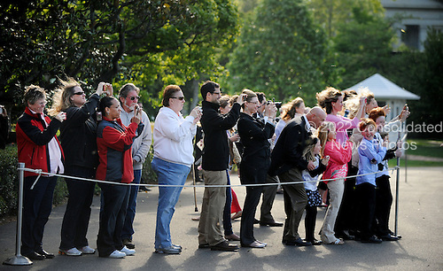 Guests take pictures of United States President Barack Obama as he departs the White House en route West Palm Beach, Florida on the South Lawn of the White House on April 10, 2012 in Washington, DC. .Credit: Olivier Douliery / Pool via CNP