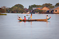 Children learn to paddle early in the floating fishing villages of Tonle Sap lake, Cambodia