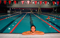 Portrait of a young woman in a college indoor swimming pool.