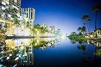 A reflection of Waikiki buildings and trees at the edge of the Ala Wai Canal, Honolulu, O'ahu.