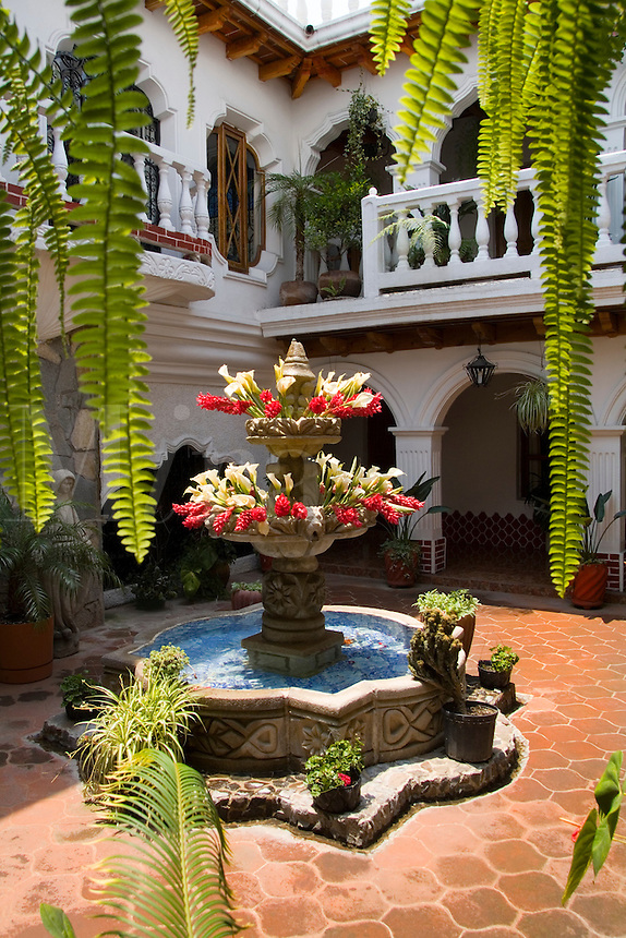 Beautiful courtyard with flowers in tourist village at the Hotel Colonial with arches and pillars in Antigua Guatemal