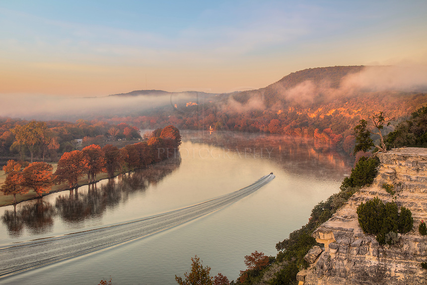 With the water smooth as glass, a lone boater glides down the Colorado River near Austin, Texas' 360 Bridge. The air was cold and the fog drifted through the river valley as the sun lit the orange and red Autumn colors.
