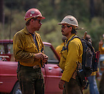 September 2, 1987 Buck Meadows, California – Stanislaus Complex Fire -- Sierra Hotshots Captain Mike Freed discusses backfire plan for the evening. The Stanislaus Complex Fire consumed 28 structures and 145,980 acres.  One US Forest Service firefighter, David Ross Erickson, died from a tree-felling accident.