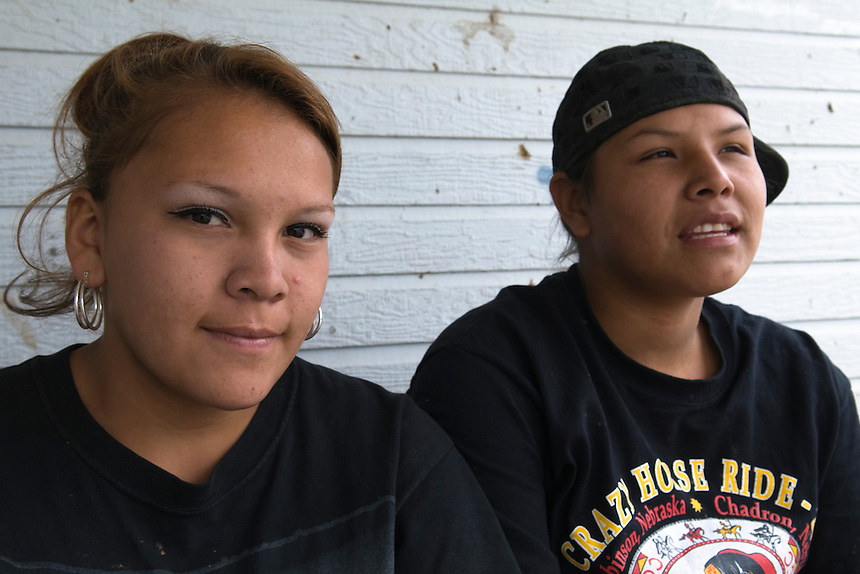 Sandra Martinez,16 (R) and her girlfriend Ann with whom she has an intimate relationships, sitting on the porch of their house, near Wounded Knee. Sandra is a student. Ann is an unemployed. Both of them are living with Sandra?s family. Like many on the Reservation, they lack money. Sandra receives two dollars for every piece of bead work she sells to tourists at table by the road. Both are dreaming to leave the Reservation and may sign up for the Army, a way they see to make more money.