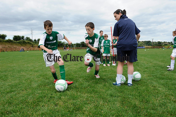 Conor Ludden and David Monaghan chase the ball  for trainer Mary Allen during the FAI/NIB Summer Soccer School at Cassidy park, Ennis. Photograph by John Kelly.