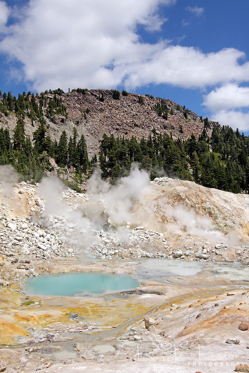 Steam rises from fumaroles alongside boiling pools in the Bumpass Hell Geothermal Area of Lassen Volcanic National Park.