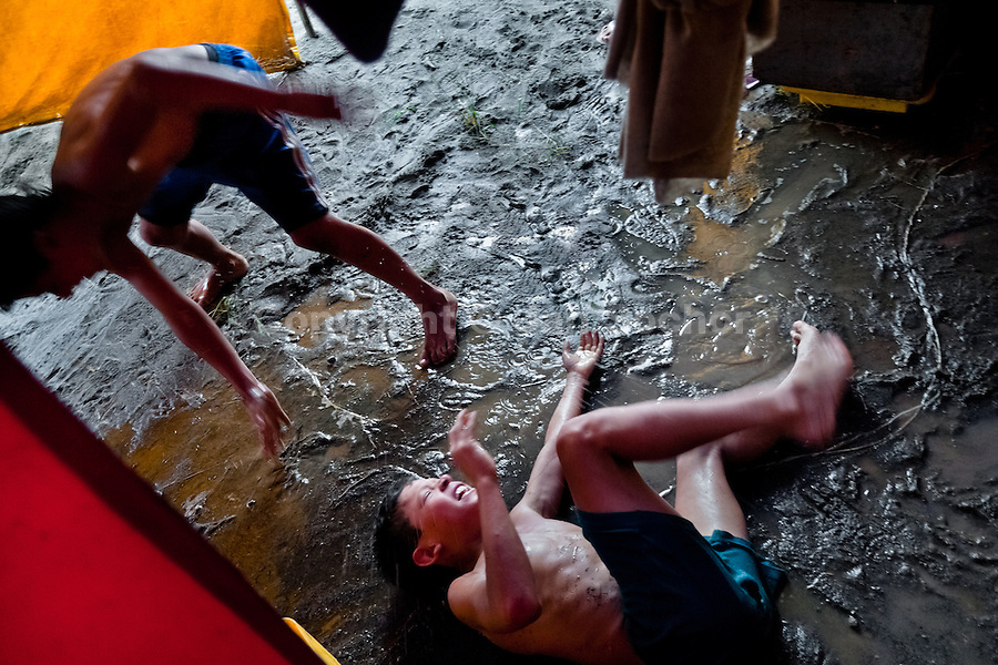 A Colombian boy falls into a mud during a friendly fight at the Circo Anny, a family run circus wandering the Amazon region of Ecuador, 4 July 2010. The Circo Anny circus belongs to the old-fashioned traveling circuses with a usual mixture of acrobat, clown and comic acts. Due to the general loss of popularity caused by modern forms of entertainment such as movies, TV shows or internet, these small family enterprises balance on the edge of survival. Circuses were pushed away and now they have to set up their shows in more remote villages. The circus art and culture is slowly dying.