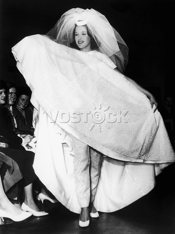 BEATNIK WEDDING GOWN, 1960. Model showing a wedding attire with blue motorcycle pants, supposedly favored by beatniks, at a teenage bridal show in London, England, 1960.