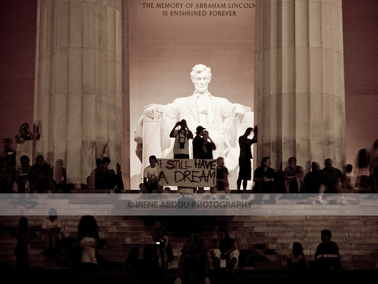 "A group of visitors to the Lincoln Memorial spontaneously hold up a sign saying, ""I Still Have a Dream."""