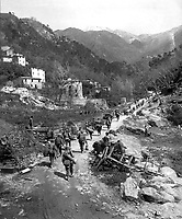 Moving up through Prato, Italy, men of the 370th Infantry Regiment have yet to climb the mountain which lies ahead.  April 9, 1945.  Bull. (Army)<br /> NARA FILE #:  111-SC-205289<br /> WAR &amp; CONFLICT BOOK #:  1030