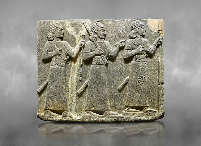 Hittite relief sculpted orthostat stone panel of Royal Buttress Basalt, Karkamıs, (Kargamıs), Carchemish (Karkemish), 900-700 B.C. Warriors. Anatolian Civilisations Museum, Ankara, Turkey.<br /> <br /> Three figures each with a long dress, a thick belt and curly hair. The figure in front holds a spear with a broken tip in his left hand and a leafy branch in his right hand. The figure in the middle made his left hand a fist, and he carries a tool with his right hand at the level of his head. They are followed with a figure holding a sceptre in his left hand. All three have each a long sword at their waist. <br /> <br /> Against a grey art background.