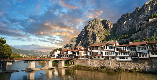 Ottoman villas of Amasya along the banks of the river Yeşilırmak, below the Pontic Royal rock tombs and mountain top ancient citadel at sunset, Turkey