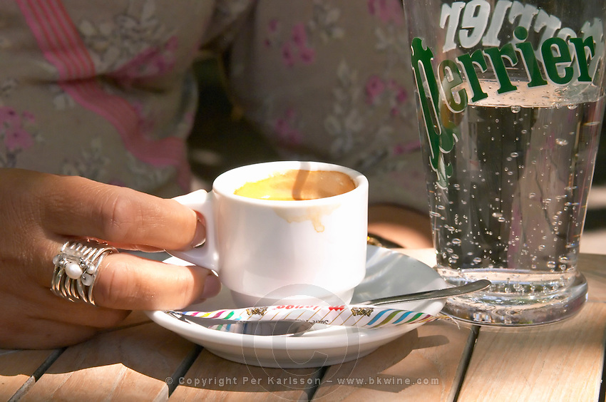 An espresso coffee cup and a glass of Perrier water on a cafe table in sunshine, a woman's hand with a big silver ring holding the cup Toulon Var Cote d'Azur France