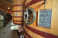 Oak barrels and big foudre fermentation vats in the winery, the plinth decorated with the winery symbol the boar, chalkboard sign indicating that the vat contains Syrah 2003, Chateau Puech-Haut, Saint-Drezery, Coteaux du Languedoc, Languedoc-Roussillon, France