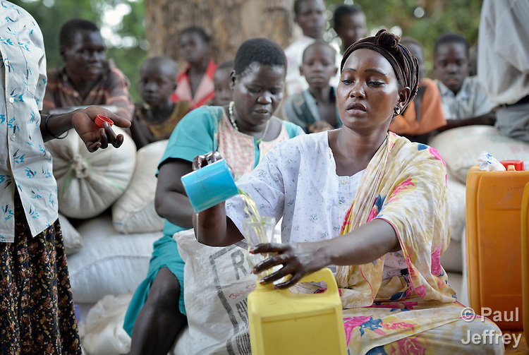Umjuma Ramadan pours cooking oil into individual containers during the distribution of food and non-food items to displaced families in Kotobi, South Sudan. The families were displaced by political violence that broke out in December 2013 and quickly fractured regions of the young nation along ethnic and tribal lines. Ramadan fled from the nation's capital, Juba. Finn Church Aid, a member of the ACT Alliance, provided materials for this aid distribution. The ACT Alliance is providing a variety of services to internally displaced families throughout the country.