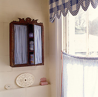 A collection of ceramics in an antique cupboard complete the blue and white theme of this bathroom