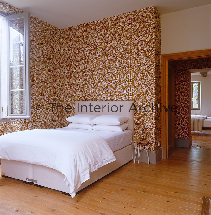 A boldly patterned Eley Kishimoto designed wallpaper covers the walls of a simply furnished bedroom