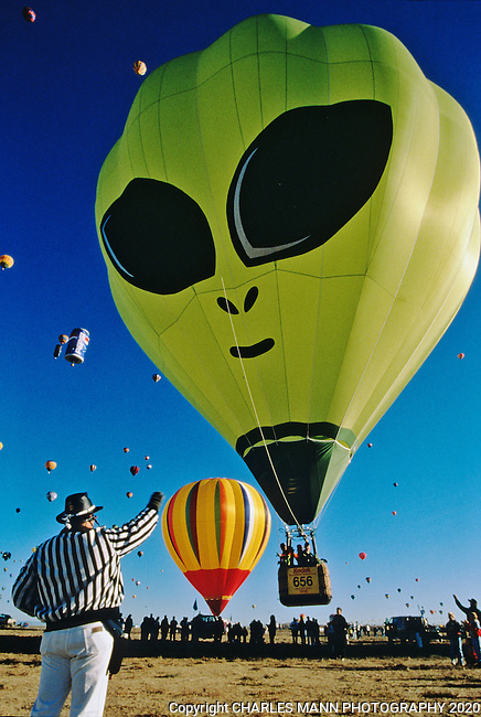 A zebra, a balloon launch event official gives the all clear to a UFO Alien balloon to launch at the Albuquerque International Hot Air Balloon Fiesta