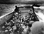WORLD WAR II WWII EUROPEAN THEATER D-DAY ALLIED FORCES U.S. TROOPS AMERICAN SOLDIERS CROUCHING DUCKING BEHIND BULWARK BARGE LANDING CRAFT NORMANDIE LANDINGS NORMANDY INVASION SEABORNE AMPHIBIOUS ASSAULT LANDING OPERATION OVERLORD D-DAY