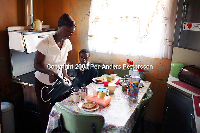 SOWETO, SOUTH AFRICA OCTOBER 25: Wilhelmina Mmesi, age 35, serves tea to her daughter Maria, age 11, early in the morning on October 25, 2006 in Soweto, Johannesburg, South Africa. She has lived with HIV/Aids since 1995 and she lives in a three-room house with her two daughters. The girls are also living with HIV. The whole family takes antiretroviral drugs, in the morning, and in the evening. She found out about her infection after her children were born, and they were both diagnosed with HIV when they were born. South Africa has one of the highest infection rates in the world. Soweto is South Africa?s largest township and it was founded about one hundred years to make housing available for black people south west of downtown Johannesburg. The estimated population is between 2-3 million. Many key events during the Apartheid struggle unfolded here, and the most known is the student uprisings in June 1976, where thousands of students took to the streets to protest after being forced to study the Afrikaans language at school. Soweto today is a mix of old housing and newly constructed townhouses. A new hungry black middle-class is growing steadily. Many residents work in Johannesburg, but the last years many shopping malls have been built, and people are starting to spend their money in Soweto.  .(Photo by Per-Anders Pettersson/Getty Images).