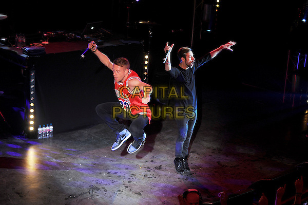 Ben Haggerty and Ryan Lewis of Macklemore and Ryan Lewis, performing in concert, Shepherd's Bush Empire, London, England. .27th May 2013.on stage live gig performance music full length red sleeveless top bulls 33 jump jumping in air gesture .CAP/MAR.© Martin Harris/Capital Pictures.